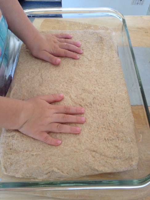 The two-year-old helps to pat the dough gently into the shape of the Pyrex pan