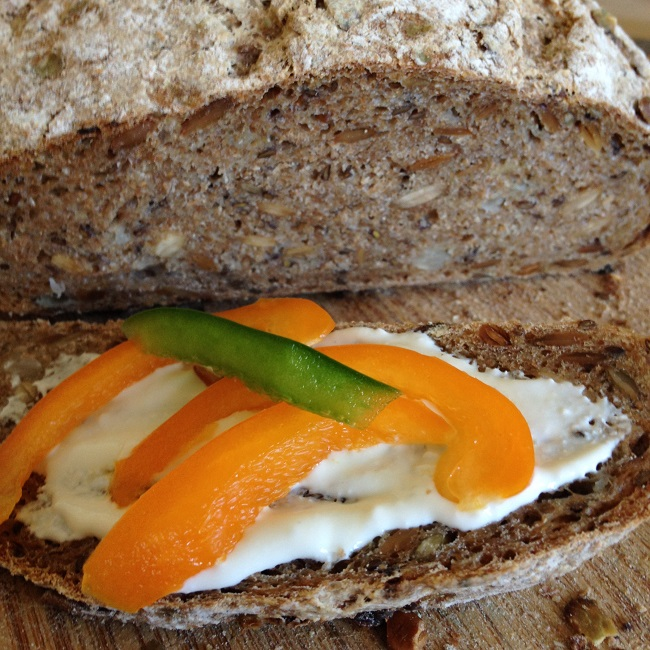 Whole wheat sourdough onion seed with creamy cheese spread and crisp bell peppers