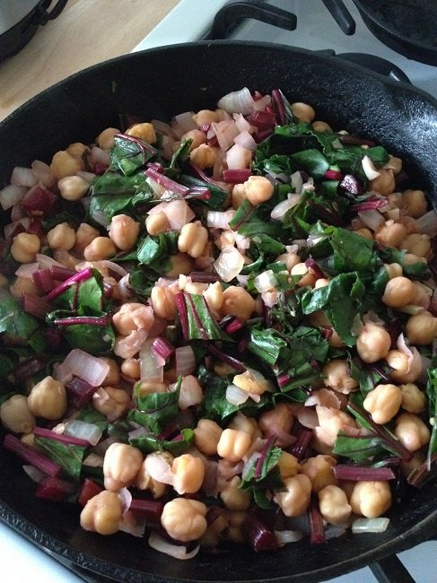 When the onions and garlic are nicely caramelized and the stems crunchy-tender, add the rest of the greens, the chickpeas and the vinegar