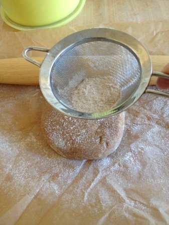 Use a fine sieve to dust the parchment paper and dough lightly