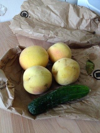 Four small, unripe peaches and a limp pickling cucumber