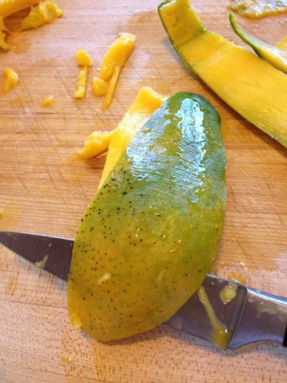 Peeling a mango wedge