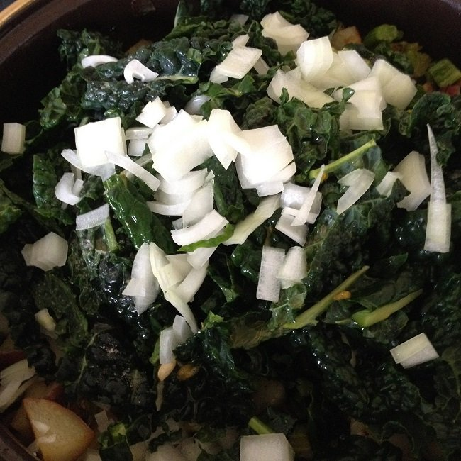 Chopped kale, onions and a squeeze of fresh lime juice, ready to stir into the vegetables in the skillet