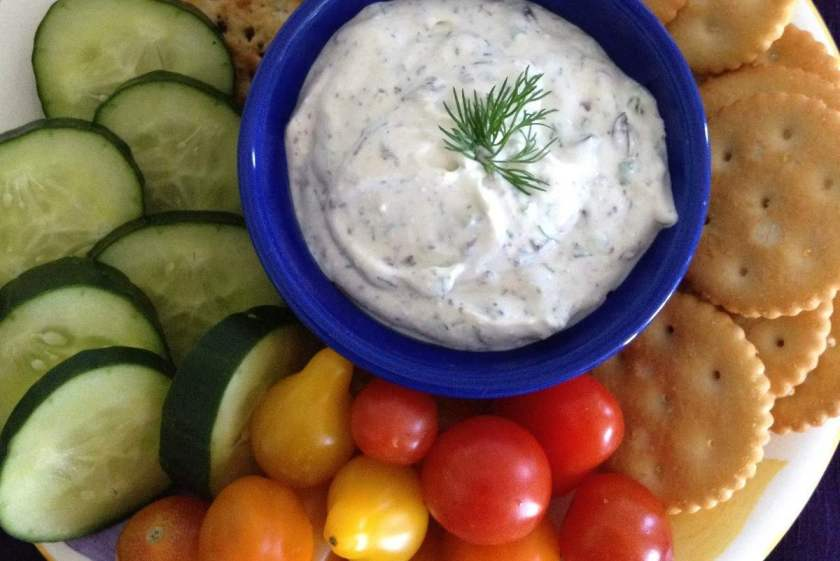 Herbed dip with chilled cucumbers, orange, red and yellow tomatoes and organic crackers