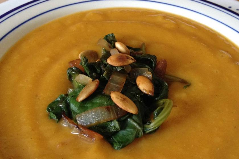 Coconut butternut squash soup with sauteed greens and roasted pippins