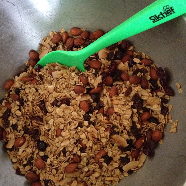 Mixing the dried cranberries and raisins into the still-hot granola