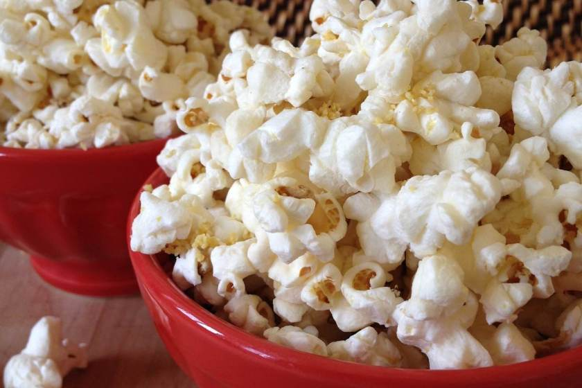 "Bowls of freshly popped corn sprinkled with vegan ""Parmesan cheese"""