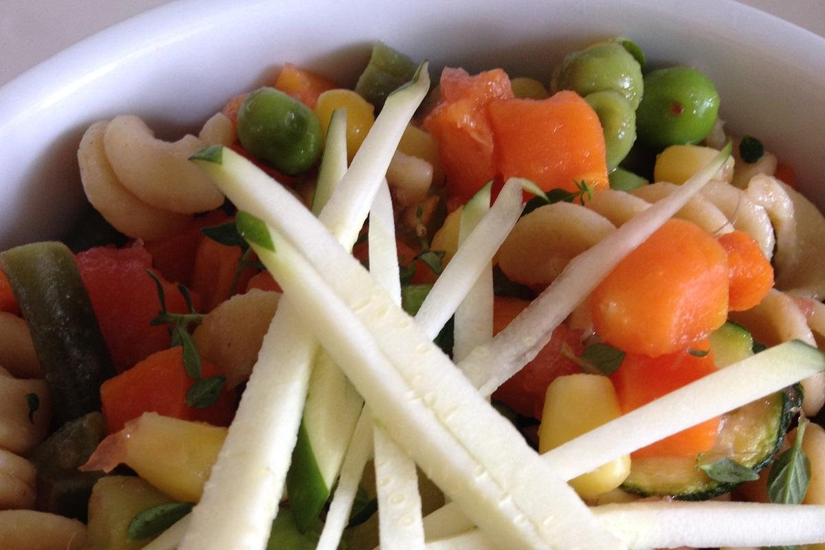 Zucchini matchstick garnish with fresh thyme on veggie pasta salad