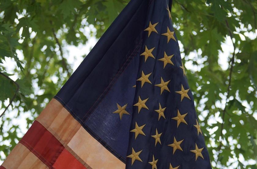 US Flag with sun-dappled trees